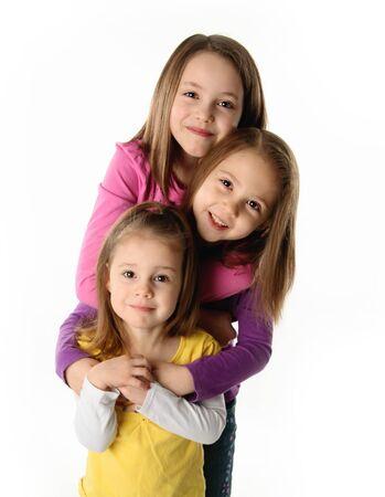 ni�os riendose: Tres j�venes hermanas lindos abrazos entre s�, aislados en blanco