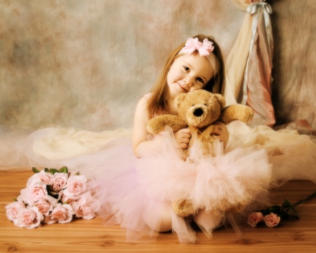 pink teddy bear: Adorable little girl dressed as a ballerina in a tutu, hugging a teddy bear sitting next to pink roses.