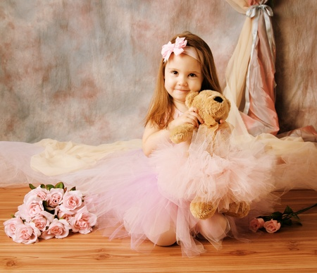 Adorable little girl dressed as a ballerina in a tutu, hugging a teddy bear sitting next to pink roses. photo
