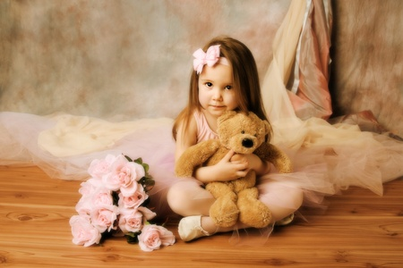 Adorable little girl dressed as a ballerina in a tutu, hugging a teddy bear sitting next to pink roses. Stock Photo - 8552616