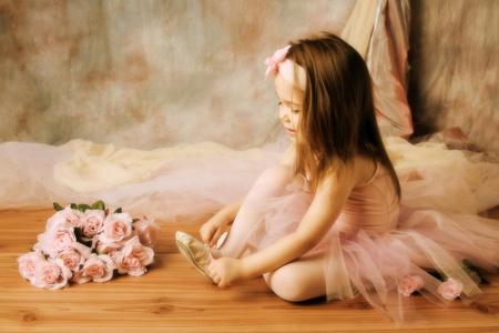 zapatillas ballet: Adorable ni�a vestida como una bailarina en un tut� atar sus zapatillas de ballet Foto de archivo