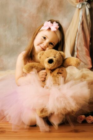 Adorable little girl dressed as a ballerina in a tutu hugging a teddy bear