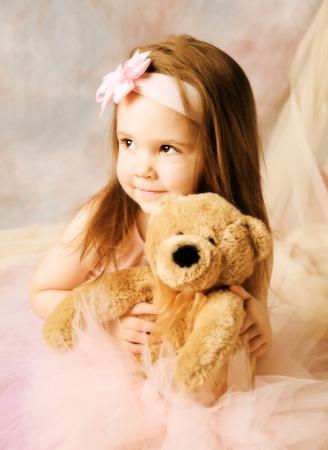 Adorable little girl dressed as a ballerina in a tutu and bow headband hugging a teddy bear.