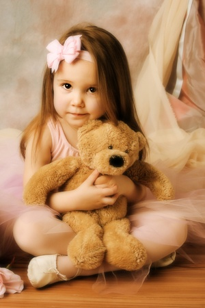Adorable little girl dressed as a ballerina in a tutu hugging a teddy bear photo