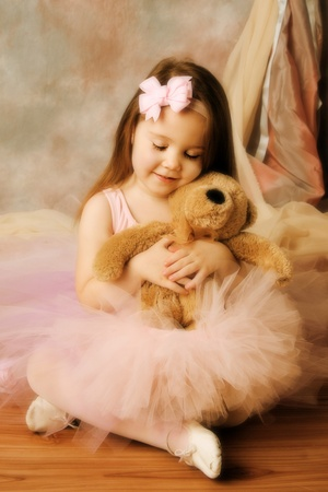 Adorable little girl dressed as a ballerina in a tutu hugging a teddy bear