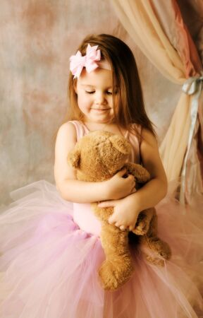 Adorable little girl dressed as a ballerina in a tutu hugging a teddy bear. photo