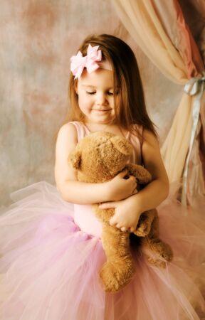 Adorable little girl dressed as a ballerina in a tutu hugging a teddy bear. photo