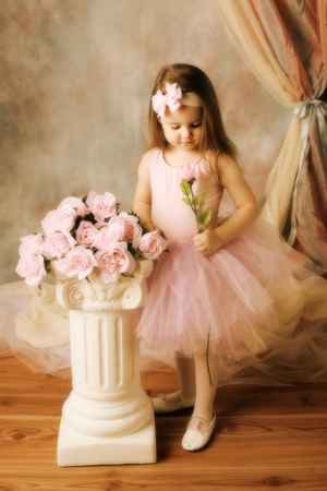 Adorable little girl dressed as a ballerina in a tutu standing next to pink roses. Stock Photo