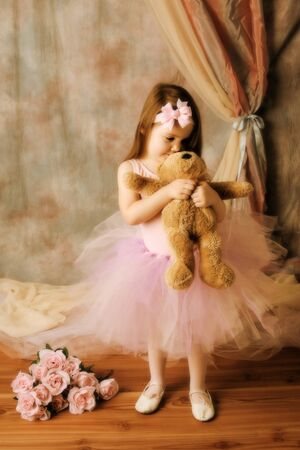 Adorable little girl dressed as a ballerina in a tutu standing next to pink roses. Zdjęcie Seryjne