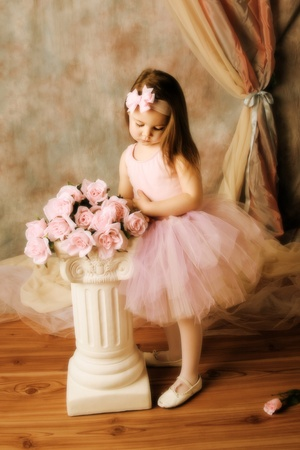 Adorable little girl dressed as a ballerina in a tutu standing next to pink roses. photo