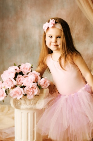 Adorable little girl dressed as a ballerina in a tutu standing next to pink roses. Stock Photo - 8534021