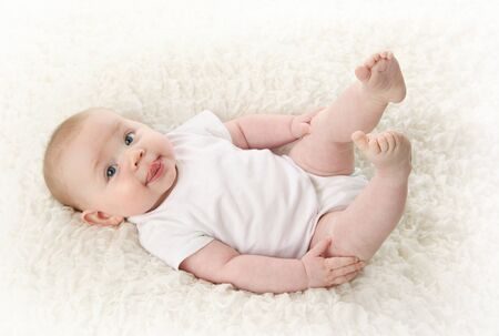 Portrait of a cute young baby lying on back over a white blanket, wearing a bodysuit shirt. Sticking tongue out.