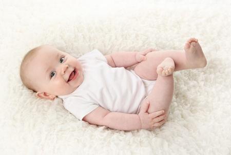 pie bebe: Retrato de un lindo beb� joven acostado arriba sobre una manta blanca, usando una camisa nadar�a