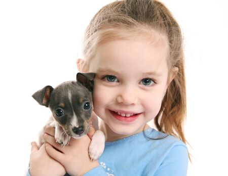 Portrait of an adorable young girl smiling holding a cute tiny rat terrier puppy