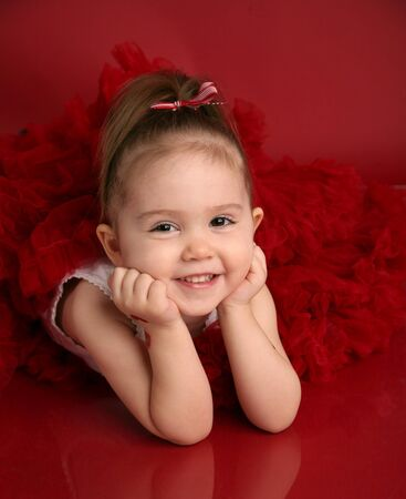 animal tutu: Portrait of an adorable little girl dressed in red on a red background for Valentines day or Christmas