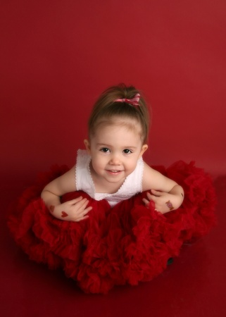 Portrait of an adorable little girl dressed in red on a red background for Valentines day or Christmas