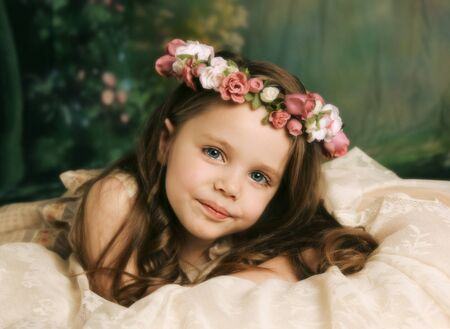 portrait young girl studio: Elegant portrait of a beautiful little girl with a rose flower halo lying on cream lace
