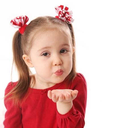 Portrait of a cute preschool girl blowing a kiss, wearing red and pigtails dressed for Valentines day