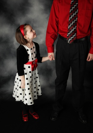 Little girl holding her daddys hand looking up at him adoringly, wearing red and black polka dot dress Stock fotó