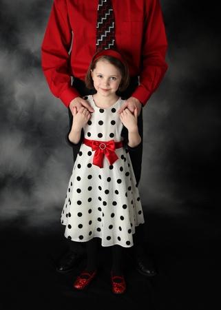pere et fille: Adorable petite fille debout devant son p�re tenant entre ses mains.