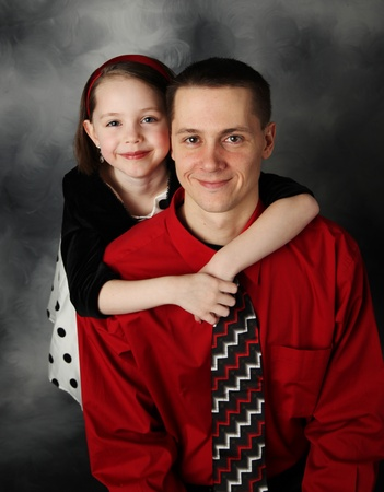 Portrait of adorable little girl and handsome father in dressy clothing hugging photo