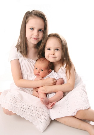 Portrait of three sisters, two little girls with a newborn all dressed in white dresses