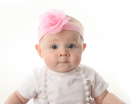 Portrait of an adorable baby girl sitting in a pink and white hatbox wearing a white shirt, pearl necklace, and pink headband with rose photo