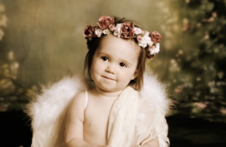 baby girls smiley face: Elegant vintage style portrait of a baby girl dressed with angel wings and a flower halo headband Stock Photo