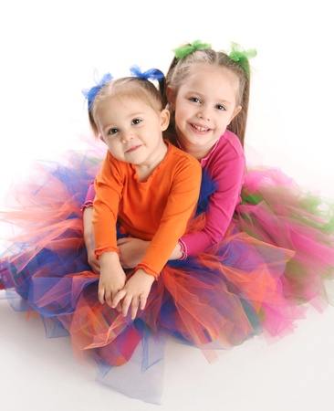Two adorable sisters dressed in bright colorful tutus sitting down hugging each other, isolated on white