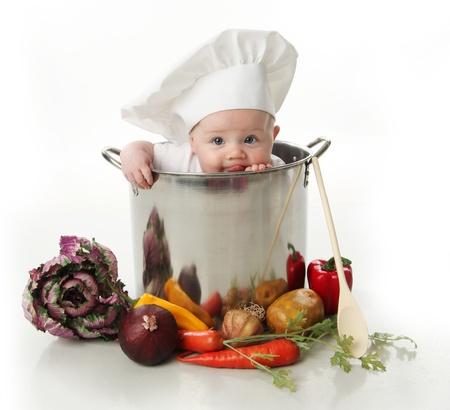 bebe sentado: Retrato de un beb� sentado llevaba un sombrero de chef sentado dentro y lamiendo una gran olla stock rodeada de verduras y alimentos, aislados en blanco Foto de archivo