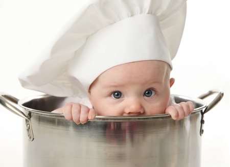 Close up portrait of a baby sitting wearing a chef hat sitting inside a large cooking stock pot, isolated on white Stock Photo