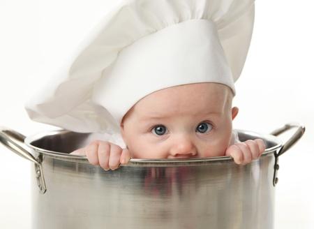vegetable cook: Primo piano ritratto di una baby sitter indossa un cappello da cuoco seduto all'interno di una grande pentola brodo di cottura, isolato su bianco
