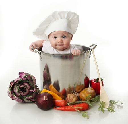 funny baby: Portrait of a smiling baby sitting wearing a chef hat sitting inside a large cooking stock pot surrounded by vegetables and food, isolated on white