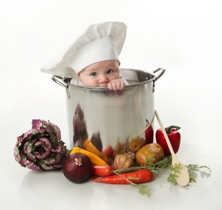 Portrait of a smiling baby sitting wearing a chef hat sitting inside a large cooking stock pot surrounded by vegetables and food, isolated on white photo
