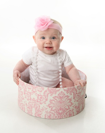 Portrait of an adorable baby girl sitting in a pink and white hatbox wearing a white shirt, pearl necklace, and pink headband with rose Stock Photo