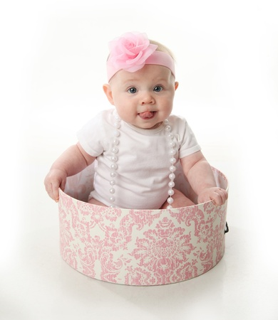 Portrait of an adorable baby girl with tongue sticking out sitting in a pink and white hatbox wearing a white shirt, pearl necklace, and pink headband with rose photo