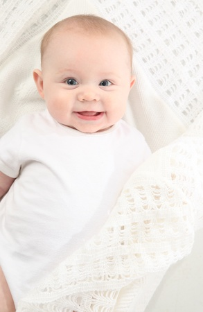 narozený: bright closeup portrait of adorable baby lying on a white handmade blanket