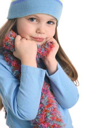 jolie petite fille: Portrait d'une belle jeune fille portant un foulard et l'hiver chapeau de la main tricot isolé sur blanc