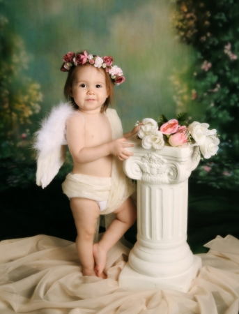 Elegant vintage style portrait of a baby girl dressed with angel wings and a flower halo headband photo