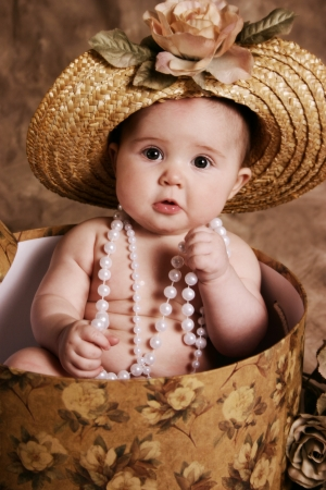 Portrait of an adorable baby girl playing dress up, sitting in a hatbox wearing a straw hat and pearl necklace photo
