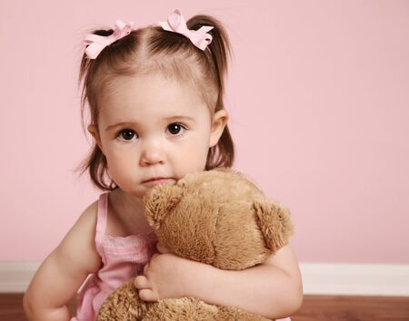 Portrait of an adorable toddler girl hugging a teddy bear on a vintage pink background photo