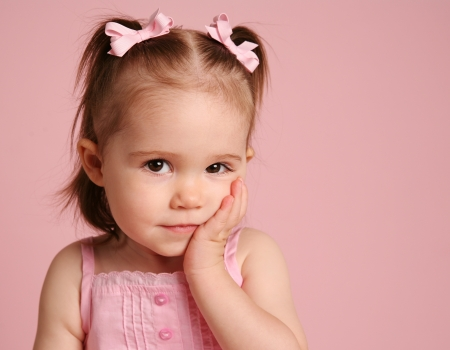 Beautiful little girl looking at the camera and posing on a pink background Standard-Bild