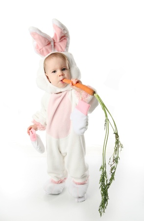 Cute young toddler girl wearing a bunny rabbit costume chewing on a carrot photo