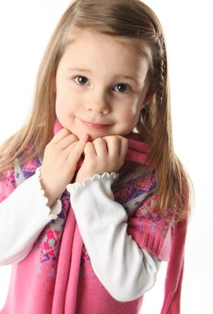 winter fashion: Portrait of a smilng adorable preschool girl wearing a knit pink dress and scarf