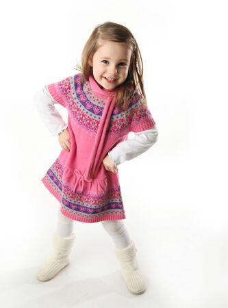 Portret van een smilng schattig preschool meisje dragen een knit roze jurk en sjaal