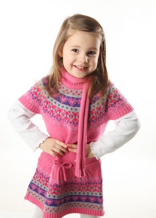 Portrait of a smilng adorable preschool girl wearing a knit pink dress and scarf photo