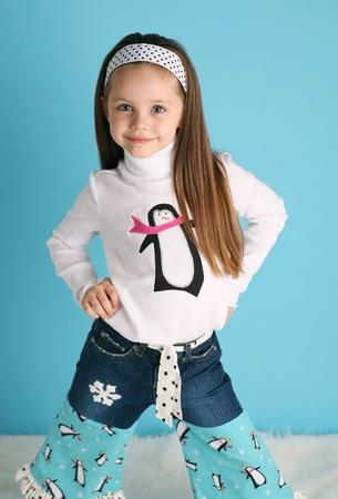 cintillos: Retrato de una ni�a adorable preescolar smilng vistiendo una camisa de ping�ino de invierno de botique a mano y pantalones vaqueros sobre un fondo azul con nieve