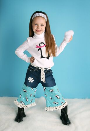 Portrait of a smilng adorable preschool girl wearing a handmade botique winter penguin shirt and jeans on a blue background with snow photo