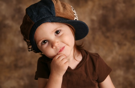 Portrait of an adorable toddler girl modeling a brown and blue jean denim hat posing for the camera photo