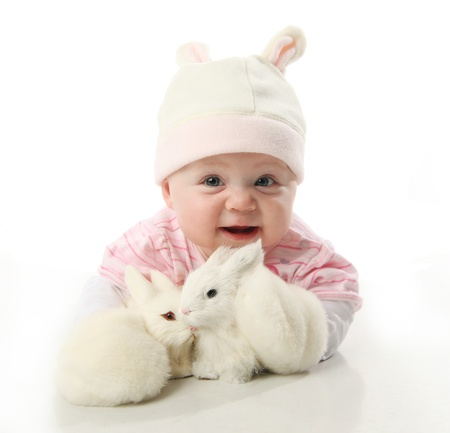 Portrait of an adorable baby girl wearing a bunny rabbit costume and petting two baby bunnies